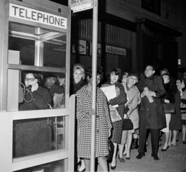 stranded-new-york-workers-wait-patiently-in-a-long-line-to-use-a-phone-booth-to-call-home